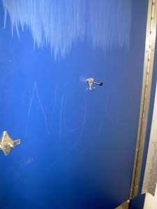 """The inside of a bathroom stall door reads """"n****r."""" Photo by Ted Swanson '83"""