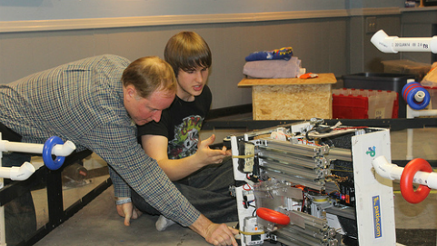 Wrecker Robotic co-captain Alec Solder '14 works with his dad John Solder, the team's mentor, on building the robot.
