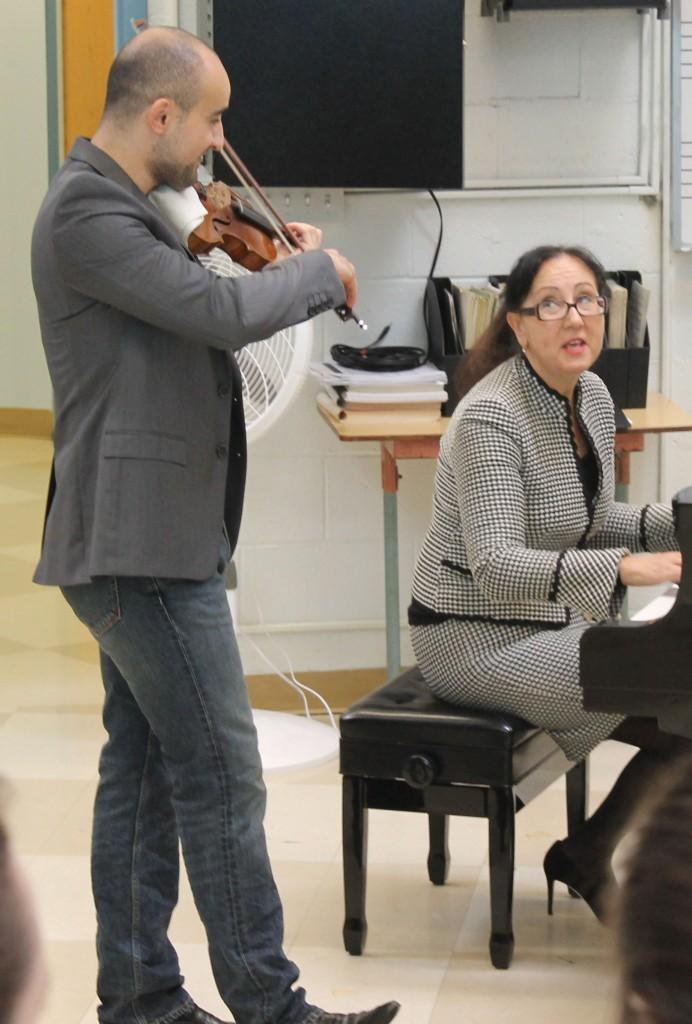 Pikazyen, accompanied by his mother on the piano, performs in front of the student audience.