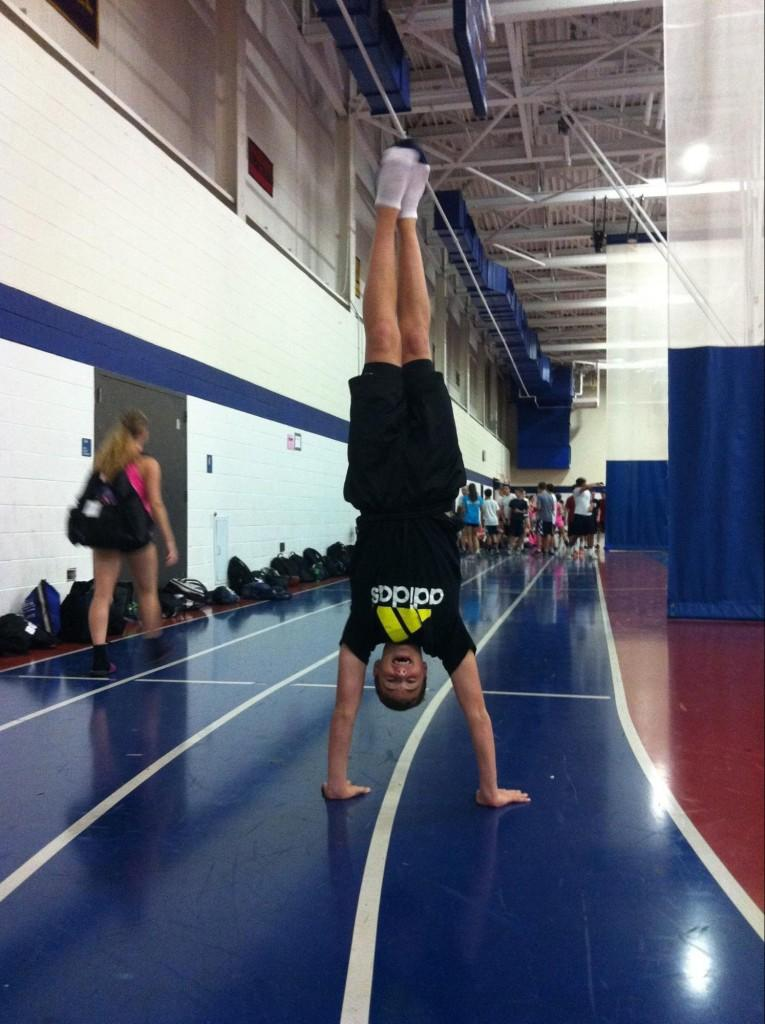 Zach+Wallace+%E2%80%9816+performs+a+handstand+before+cheerleading+practice.