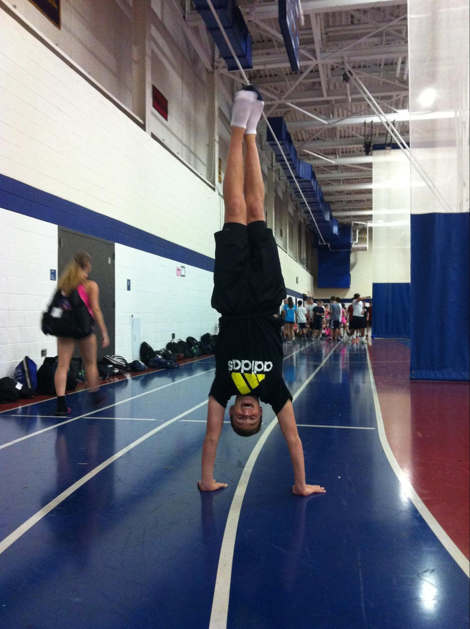 Zach Wallace '16 performs a handstand before cheerleading practice.