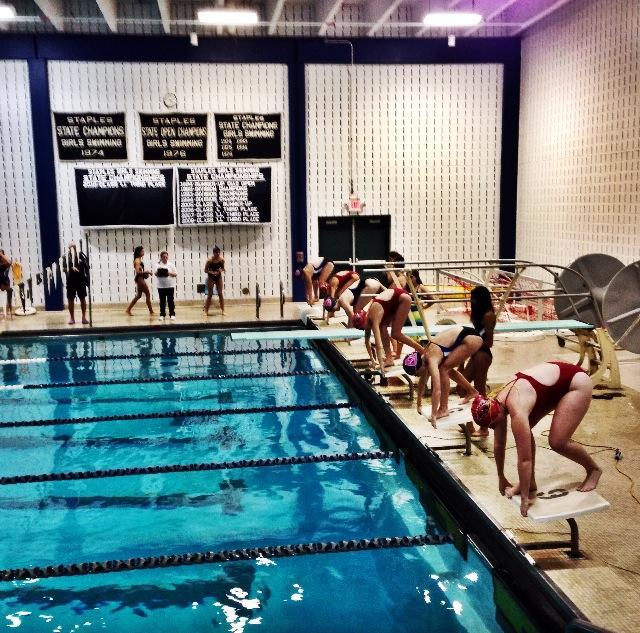 In+high+anticipation+and+excitement%2C+the+swimmers+prepare+to+launch+into+the+water+as+the+crowd+cheers+on.