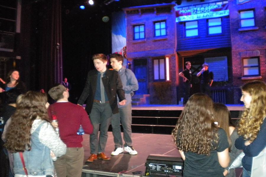 Actors in Avenue Q and audience members hang out on stage after their first performance ended.