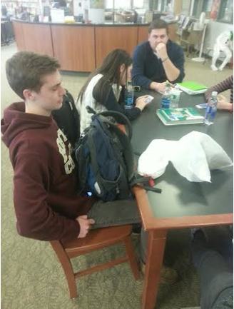 Patrick Beusse '15 sits in the library with his trash bag.