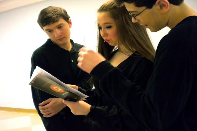 Zoe Fox '16, who played Care-ee bear, Garrick New'16, who played Pooh, and Aaron Samuels '16, who played Paddington, look through the playbill for their names and ads during a break.