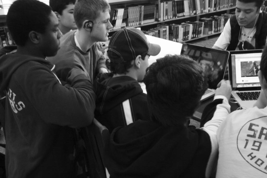 MAD FOR MADNESS: A group of freshman  boys intently watch the action in the library (above) and the hallway (right) to see what teams dominated on March 20w, the first day of the NCAA tournament. Every period, students can be found throughout the school glued to their computer screens.  PHOTOS BY JUSTINE SELLIGSON '15