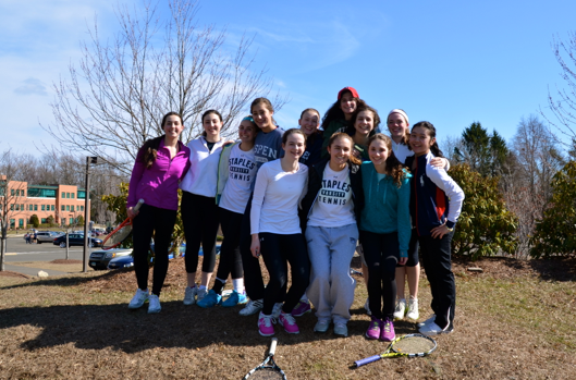The former varsity members of the girls' tennis team and the new girls trying out all pose for a photo during a water break.