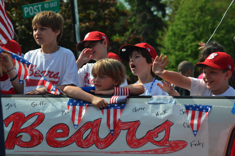 Several little league players waved to the crowd and clutched onto their American flags from the back of a decorated pick-up truck, representing their team: The Bears.