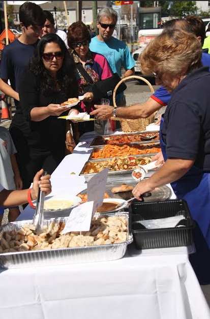 Tutti's employees hand out a wide array of samples to a long line of eager customers.