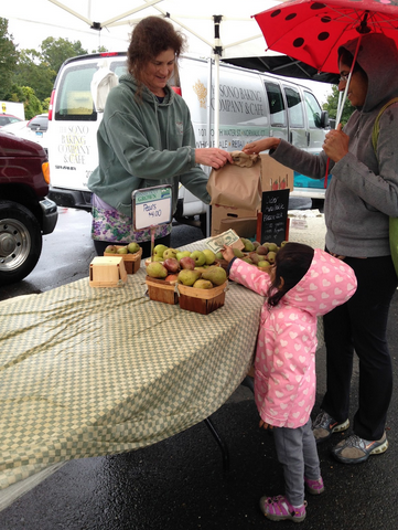 A+young+shopper+pays+for+the+pears+at+the+Connecticut+Grown+booth.%0D%0A