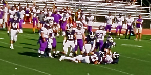 Staples players pile on a Westhill player.