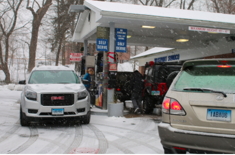 Lines for gas flowed into the streets as the storm began to make its mark Monday afternoon.