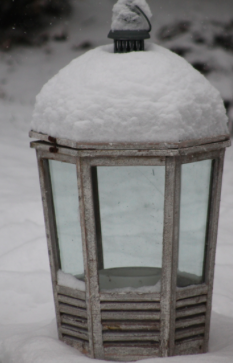Heavy snow rests on top of an outdoor light, the snow beginning to accumulate at a very fast rate.