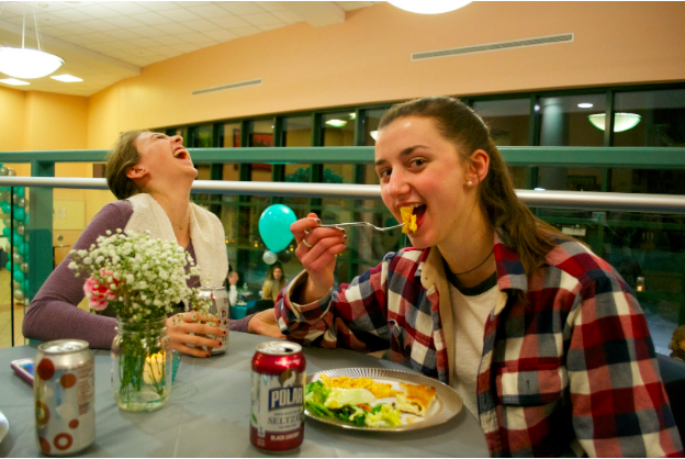Students Rachel Morrison '16 and Olivia Daytz '16 enjoy the food and beverages served prior to the fashion show and videos projected in the auditorium.