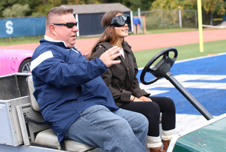 Westport Police Officer Ned Batlin prepares Claire Lonergan '17 for her drive through a course in a golf cart while wearing goggles that simulate the vision of a person after 2 to 6 beers. Photo by Jane Levy.