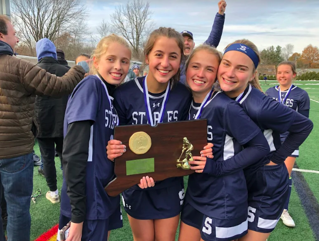 The Staples field hockey team secures the title of state champions after their game against Cheshire.