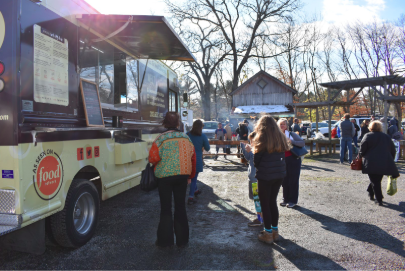 People enjoy food from the food trucks at the local Westport Farmer's Market.