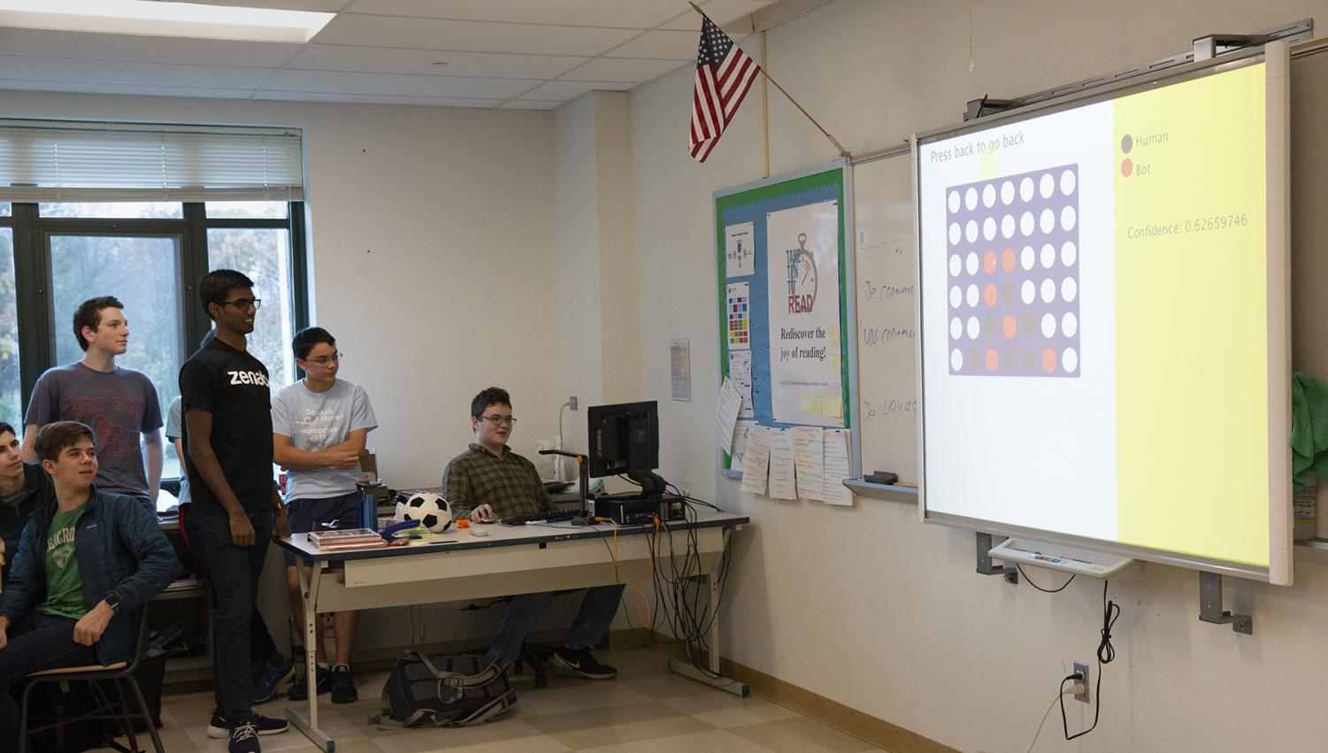 A team at the Code-a-thon presents their final design to a panel of judges. Their program, which included a virtual checkers match against a bot, won first place.