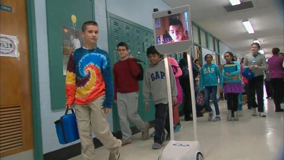 Students walk in hallways to get to class as usual, while their peer who was out sick is wheeled around on a rolling screen. This student was able to keep up in class and is another futuristic alternative to keep kids up to date when they have to miss class.