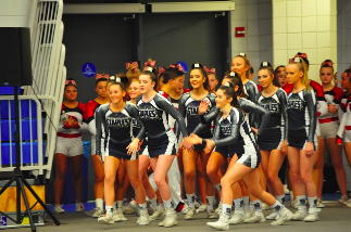 The cheer team gets excited as they begin to run onto the mat and start their performance at regionals.   Photo contributed by Harley Bonn '21