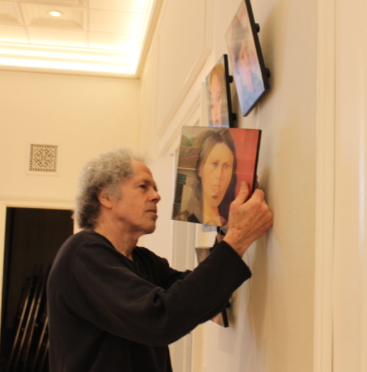 Miggs Burroughs hangs his lenticular art the day before the show.