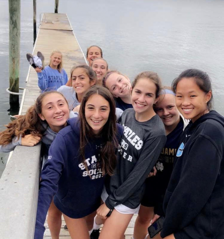 Girls' soccer team welcomes new members to the team, at beach hangout.