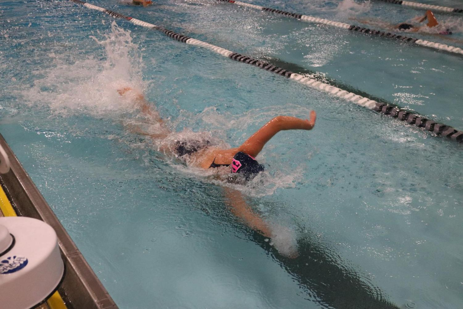A swimmer on the Staples girls' swim and dive team is racing as fast as she can in order to try and win her event. She is focusing on her technique and energy, not the possibility of her swimsuit shifting around in the water.