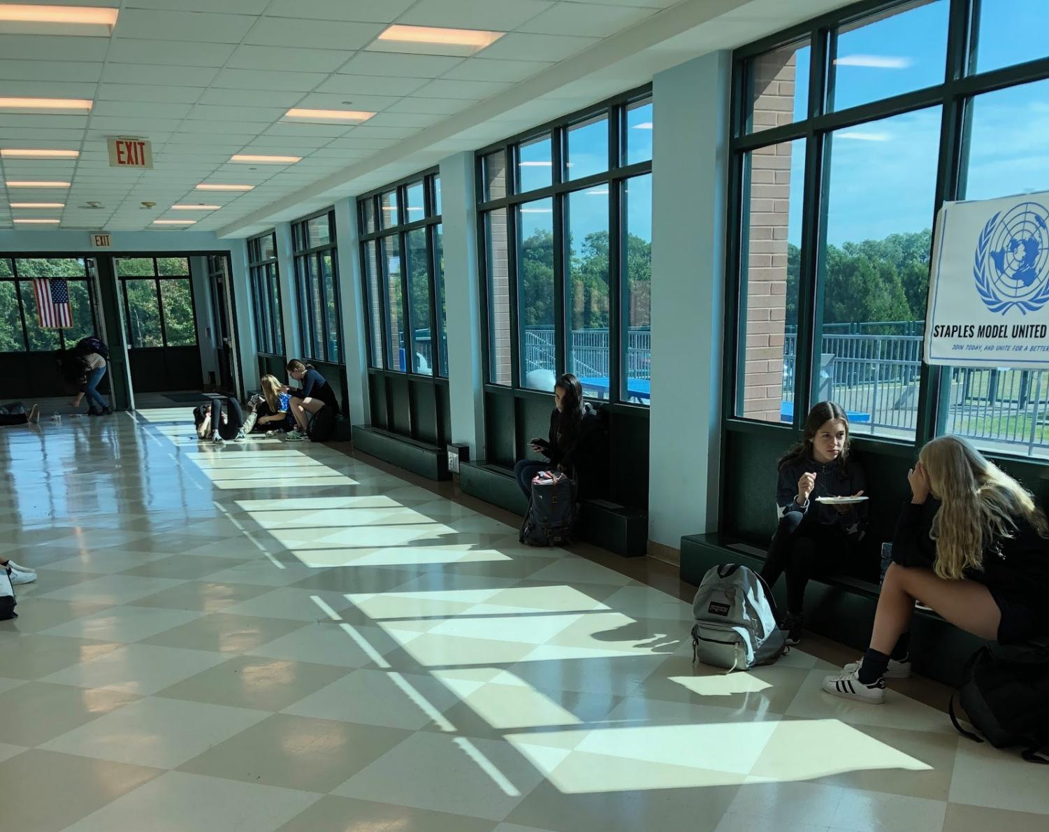 Staples students enjoy eating their lunch in the hallway surrounding the cafeteria.