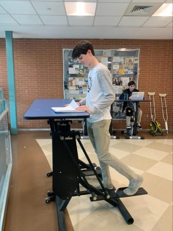 Cooper Tirola '23 uses Staples' standing desk to exercise while studying for the upcoming midterms. This example is just one of the many studying techniques explained in the podcast.
