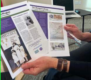 """Kathie Bennewitz, a curator for the WestportREADS exhibition """"Westport's Suffragists - Our Neighbors, Our Crusaders, displays an infographic by the Westport library about the upcoming exhibit."""