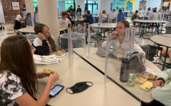 Alex Gordon '24, Ruby Kantor '24 and Alice Anderson '24 eat lunch with the new dividers to accommodate for school with COVID-19. With the new regulations, students must sit three or four to a table, with X's on every other seat.