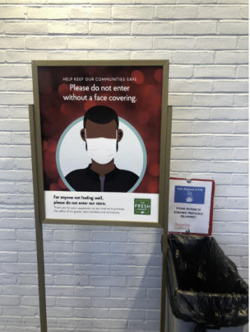 "A sign asks customers at ""The Fresh Market"" to not enter the store without a mask. Signs like these have been seen frequently in front of stores such as Home Goods and Terrain throughout the pandemic."
