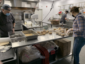 "The staff of Westport-based Pop Up Bagels works to prepare bagels for pick-up in the Manna Toast ""Hub kitchen."""