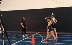 The girls' indoor track 1600 meters participants line up at the starting line.