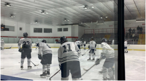 The boys' varsity hockey team warms up before one of their games. The CIAC hockey program is up and running while maintaining COVID protocols to ensure safety for all players.