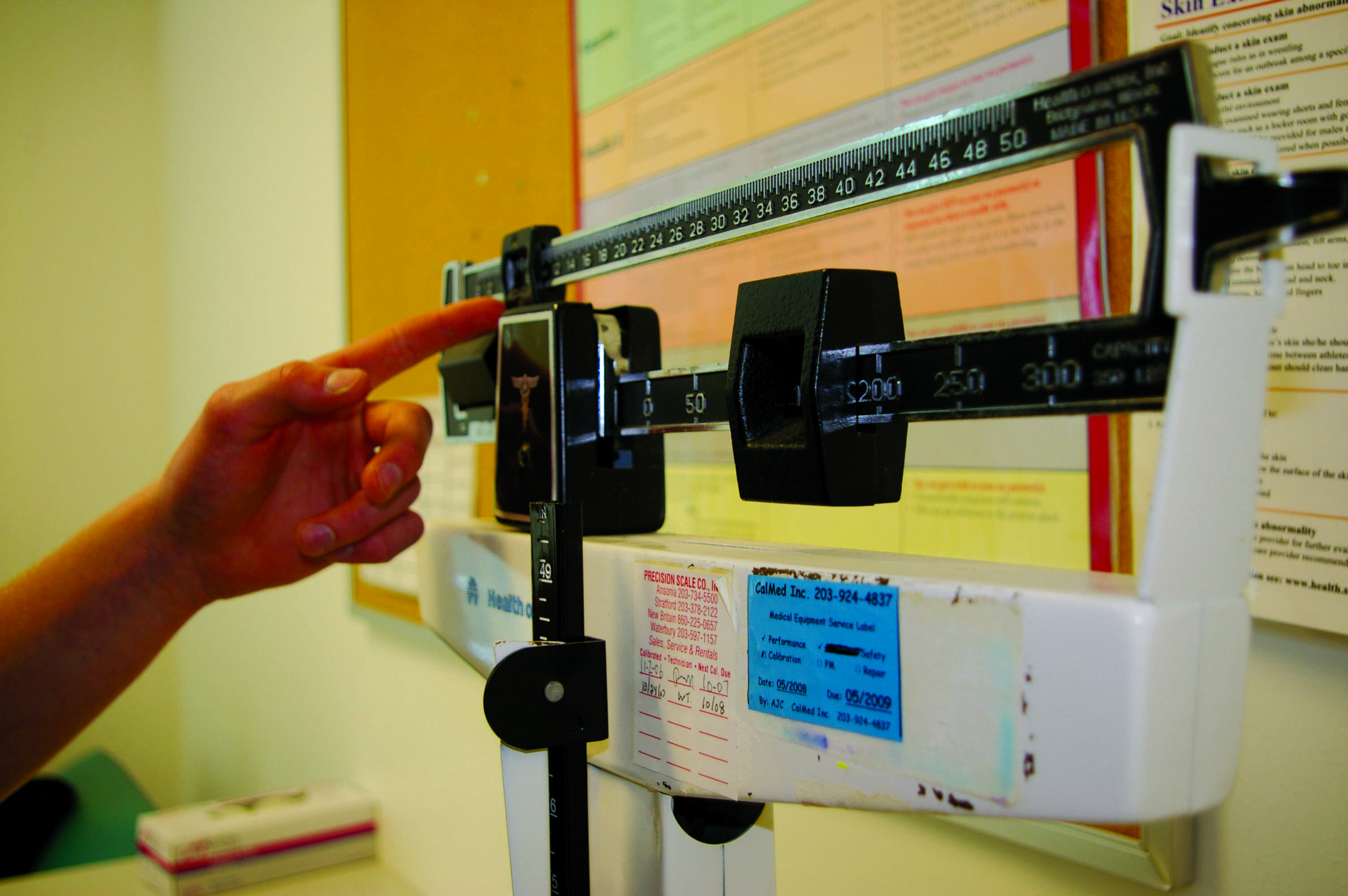 WEIGHING IN: Athletes struggle with the demands of their respective sports, often checking their weight to maintain eligibility. | Photo by Ashley Bonett '10