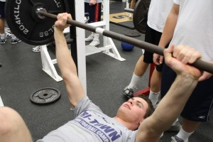 POWER LIFT: Captain Chris Coyne '11 reps weights on the bench press while training hard in the off-season. Coyne returns to the Wreckers as an All-FCIAC Defensive-End and runner up in total sacks in Connecticut. | Photo by Lucas Hammerman '10
