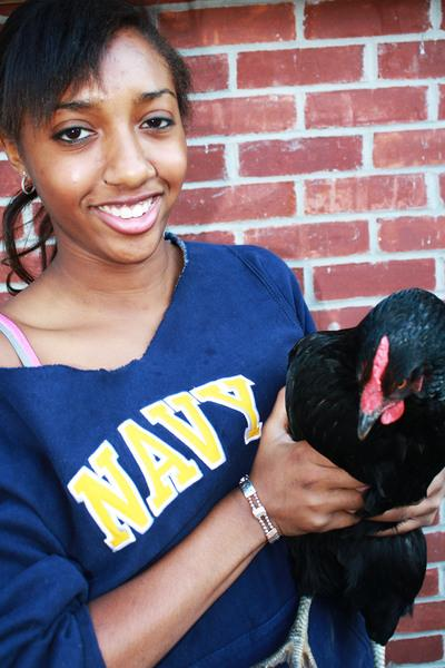 Briyana Theordore '12 embraces a chicken that her and her family have raised.   Photo by Lucas Hammerman