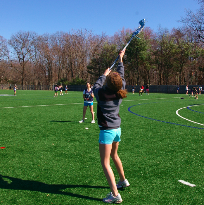 Jess Adrian '13 reaches to catch a pass as she warms up for tryouts. | Photo by Carlie Schwaeber '12