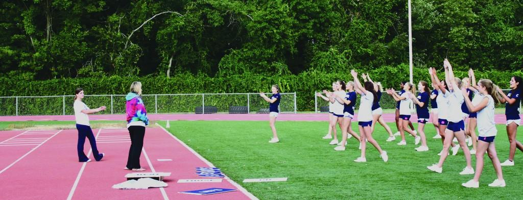 Photo By Annie Nelson '11 - New Varsity Coach,  Denise Dargel leads the Staples varsity cheerleaders in a practice cheer.