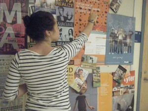 Danielle Ehrenwald '11, in a dramatization, seeks an art school that is right for her. The bulletin board across from the Four Building is a perfect place to do so.