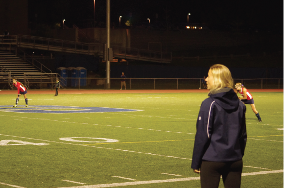 Girls' field hockey coach Ashley Delvecchio guides the team from the sidelines during their first game under the lights against Norwalk's Brien McMahon High School.