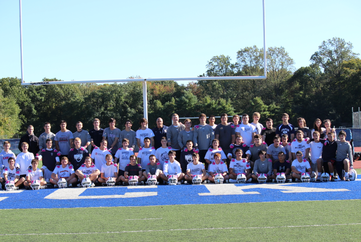 The football team shows off their pink gloves.