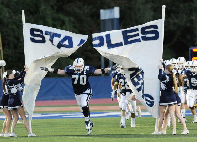 Kyle Vaughn runs through the Staples Wreckers banner.