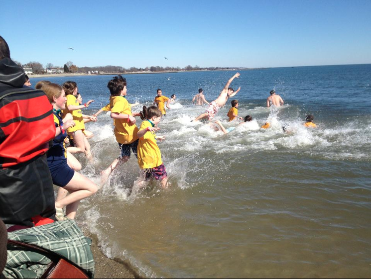 Some younger participants jump into the frigid waters at the