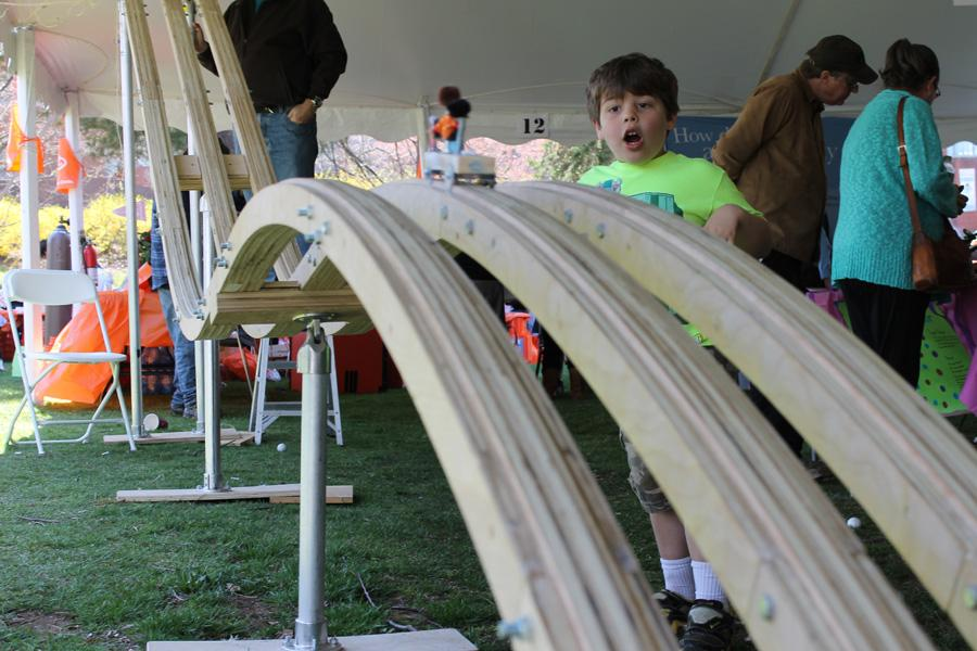 A child watches his model car rush down the track at the Nerdy Derby, a booth with a wooden race track.