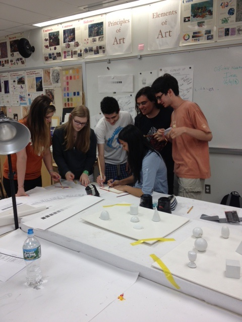 Members of the art club gather around for a meeting