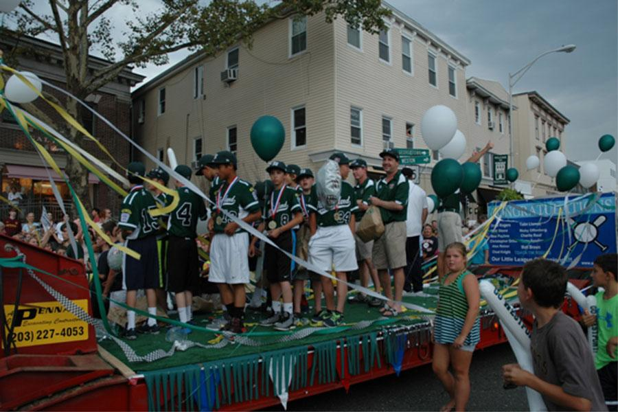Westport Little League's 12U team, which is ranked second in the nation for their division, makes their way through town while being celebrated by the lively crowds.