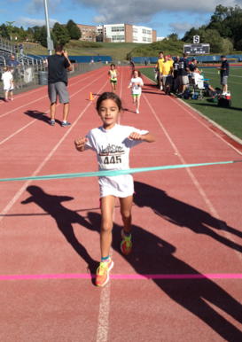 Long Lots Elementary School Student Alexandra Hackett, age six, crosses the finish line and the YMCA Strong Kids Triathlon.