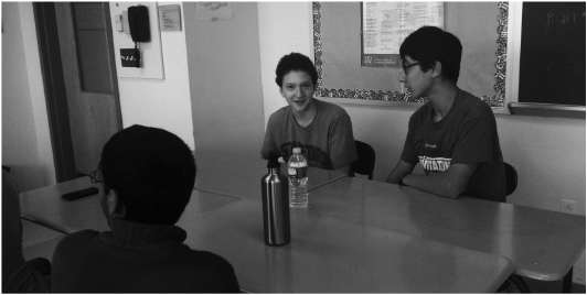 A table of sophomores Jordan Darefsky '16 (facing, far left), Jacob Klegar '16 (facing, on right) and Arjun Dhindsa '16 (back turned) are some of the underclassmen at Staples sharing courses with their older peers. (photo by Katie Cion)